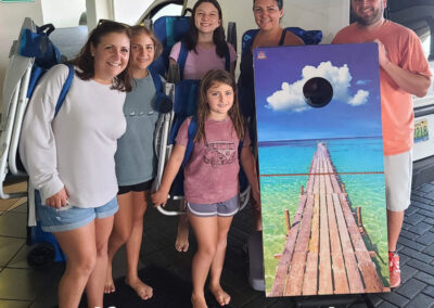 family standing together with their corn hole rental