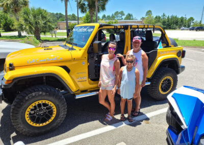 father, mother, daughter standing in front of yellow jeep wrangler