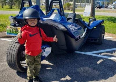 little boy with helmet on ready to ride in a blue slingshot rental
