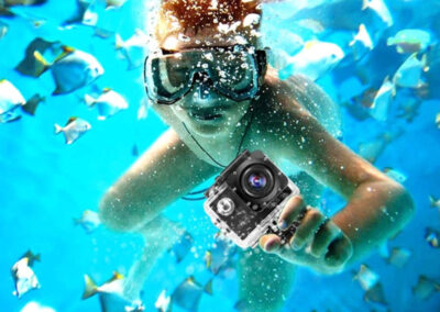 child swimming underwater with a gopro surrounded by fish